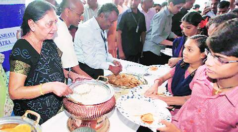 Gujarat Chief Minister Anandiben Patel serves food to children in Ahmedabad on Sunday. Source: PTI