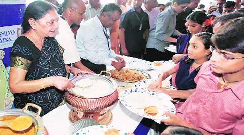 CM Anandi Patel serves food to children after the inaugration of a mid-day meal kitchen facility in Ahmedabad on Sunday. ( Source: PTI )