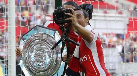 Arsenal's Santi Cazorla, right, takes a selfie with Alex Oxlade-Chamberlain as they celebrate their win against Manchester City with the trophy at the end of their English Community Shield match at Wembley Stadium in London on Sunday. (Source: AP)