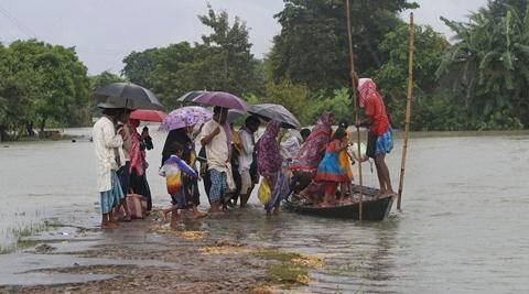 Flood affected villagers board a country boat at Gagolmari village in Morigaon district of north eastern Assam on Sunday. (Source: PTI)