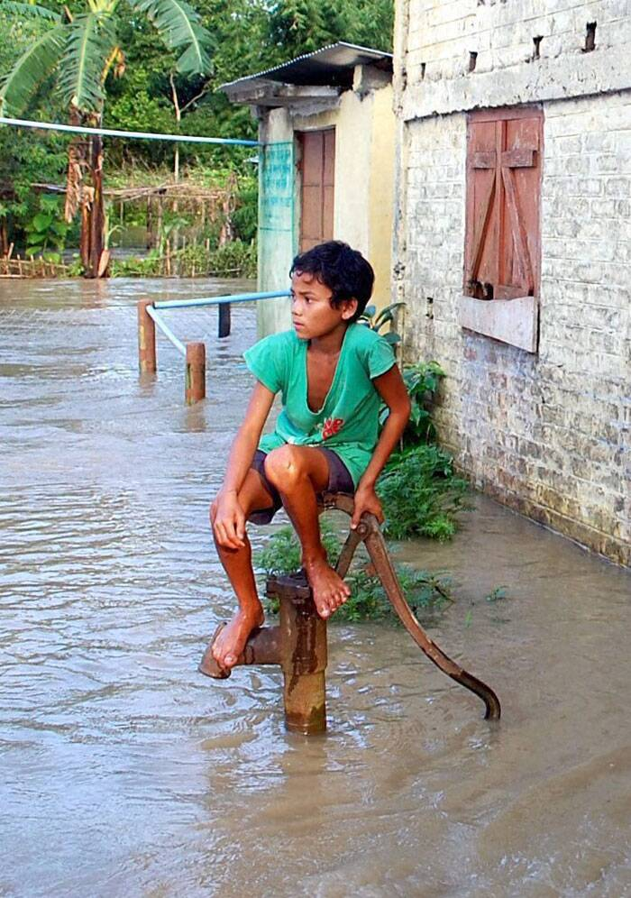 According to the State Disaster Management Authority (SDMA), a total of 1,265,449 people were affected due to floods as the surging waters of Brahmaputra and its tributaries inundated 2,093 villages in the 16 districts. This has forced 163,052 people to take shelter in 212 relief camps set up by the administrations.<br /><br /> A young boy waiting for a boat, perches himself atop a hand pump amidst flood waters in Horeghat village in Dibrugarh on Tuesday. (Source: PTI Photo)