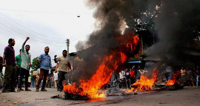 Protesters burn tyres at the National Highway 38 at Margherita in Tinsukia district on Thursday against the killing of Assamese people by suspected NSCN at Assam Nagaland border in Golaghat. (Source: PTI)