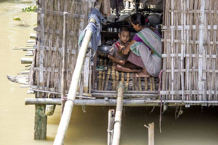 Officials said at least 10 people have died since August 18. In the latest casualty, two people died due to floods in Lakhimpur and Morigaon districts. <br /><br /> A woman redies her child to take to safety as her house partially submerged by flood waters at Afala village at Disangmukh in Sivasagar district of Assam on Tuesday.   (Source: PTI Photo)