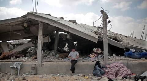 A Palestinian sits in front of a destroyed house in Rafah's district of Shawkah in the southern Gaza Strip. (Source: AP)