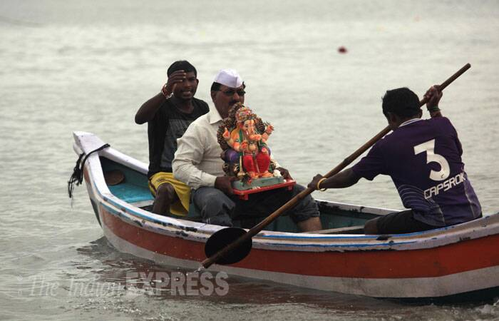 A devotee carries Ganesh idol in a boat for immersion in Mumbai. (Source: Express photo Ganesh Shirsekar)