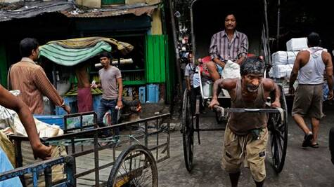 An Indian hand rickshaw puller with passenger makes his way through a traffic jam in Kolkata, India. (Source: AP photo)