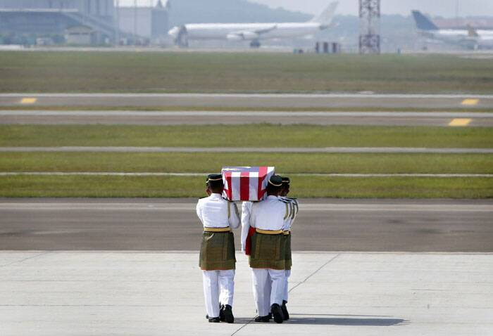The remains of a victim of the downed Malaysia Airlines flight MH17 are carried during a repatriation ceremony at KLIA airport in Sepang. (Source: Reuters)