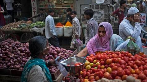 An Indian woman buys vegetables at a road side stall in New Delhi, India. (Source: AP photo)