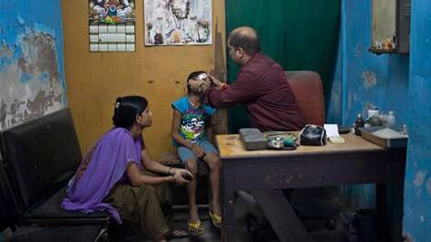 An Indian doctor treats a boy at a private clinic in New Delhi, India. (Source: AP photo)