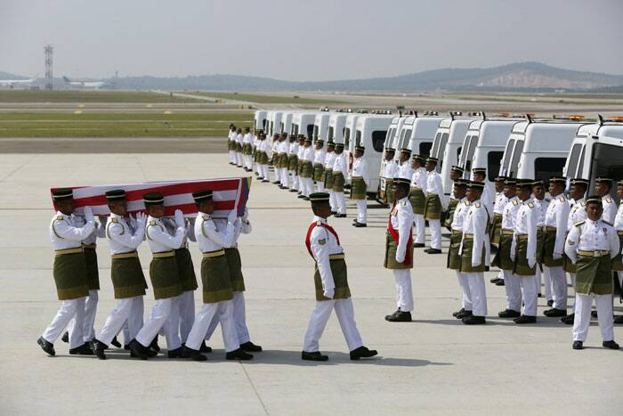 The remains of victims of the MH17 disaster are carried during a repatriation ceremony at the Bunga Raya complex of KLIA airport in Sepang. (Source: Reuters)
