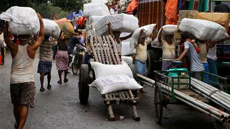Indian laborers load and offload goods outside a wholesale market in Kolkata, India. (Source: AP photo)
