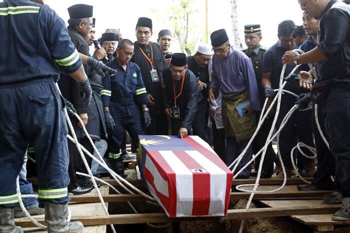 Mohamed Salleh, center, father of Nur Shazana, a crew member who was killed in the downing of the Malaysia Airlines Flight 17, touches his daughter's coffin during a burial ceremony at Taman Selatan Muslim cemetery in Putrajaya, Malaysia on Friday. <br /> Carried by soldiers and draped in the national flag, coffins carrying Malaysian victims of Flight MH17 returned home Friday to a country still searching for those on board another doomed jet and a government battling the political fallout of the twin tragedies. (Source: AP)