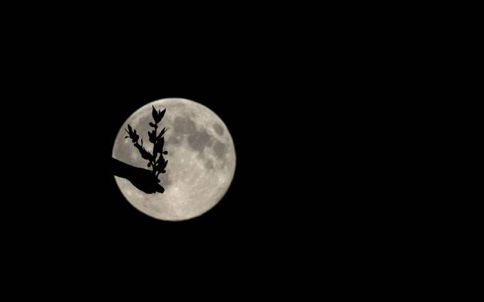 A supermoon appears behind the Angel of Peace sculpture, in London, Sunday. (Source: AP)