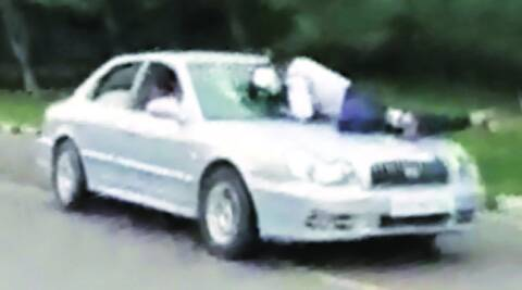 Traffic cop Davinder Singh being dragged on the bonnet of the car.  (Express archives)