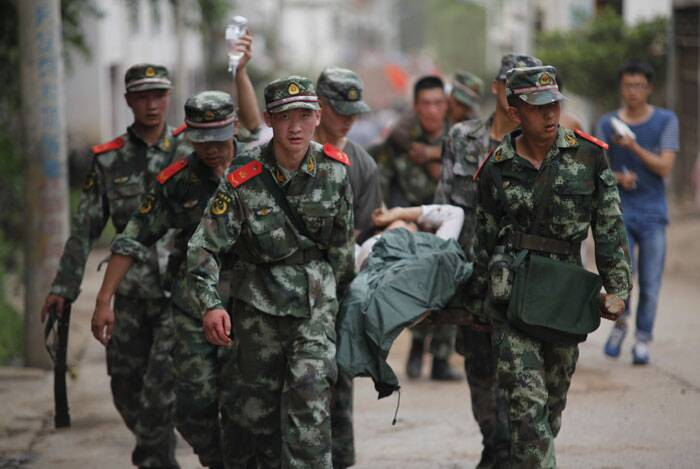 In this photo released by China's Xinhua News Agency, rescuers transport injured people after an earthquake in Zhaotong City in the densely populated Ludian county in southwest China's Yunnan Province. (Source: AP)