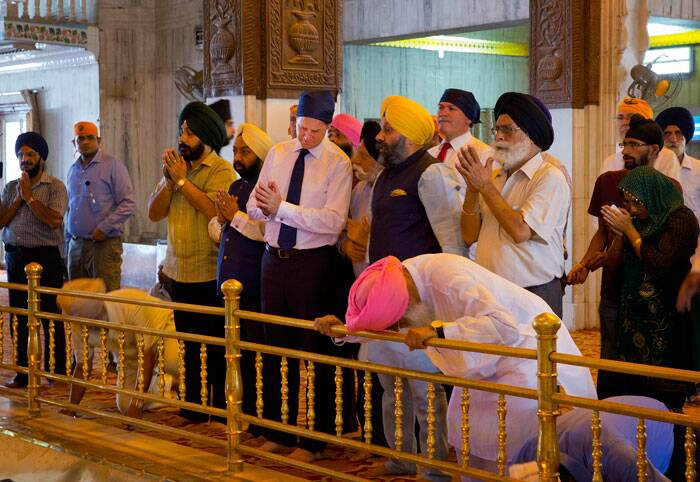 Britain's Deputy Prime Minister Nick Clegg, fifth from left, offers prayers with folded hands during his visit to the Bangla Sahib in New Delhi. (Source: AP)