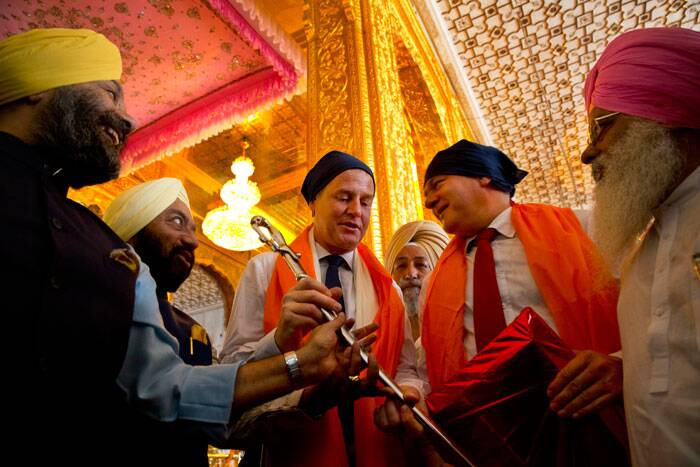 Britain's Deputy Prime Minister Nick Clegg, third left, holds a sword presented to him by temple authorities at the Bangla Sahib Gurudwara in New Delhi.  (Source: AP)
