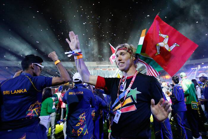 Athletes waves and hold flags as they watch the the Closing Ceremony for the Commonwealth Games Glasgow 2014.(Source: AP)