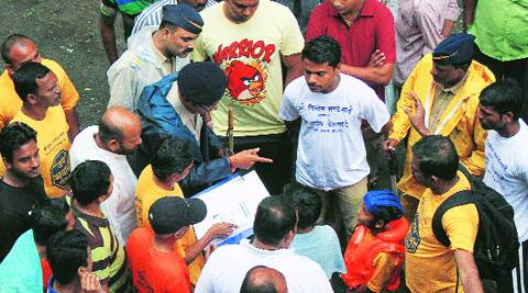 A policeman enquires with a child Govinda about his age even as a mandal member shows him his birth certificate. (Source: Express photo by Pradeep Kochrekar)