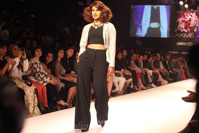 Priyanka Chopra sashayed down the ramp for Varun Bahl in black palazzo pants, crop top in the same shade teamed with sliver sequenced jacket. With a stylish hairdo and a heavy neckpiece, the actress looked her absolute best. (Source: Express photo by Dilip Kagda)