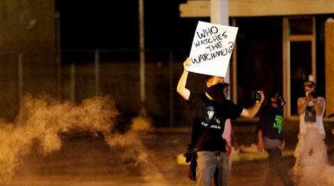 A protester stands in the street after police fired tear gas to disperse a crowd Sunday. Source: AP photo