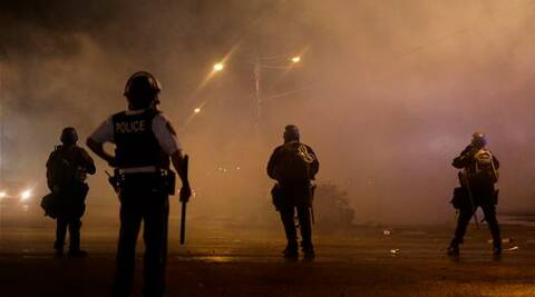 A law enforcement officer watches as tear gas is fired to disperse a crowd protesting the shooting of teenager Michael Brown in Ferguson.