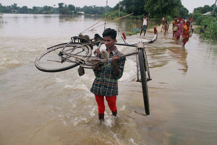A villager walks through a submerged road lifting his bicycle the flood affected Buraburi village of Morigaon district, Assam on Sunday. (Source: PTI)