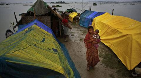 A flood affected woman carrying her child walks past her temporary shelter in a village in Assam. (Source: AP)