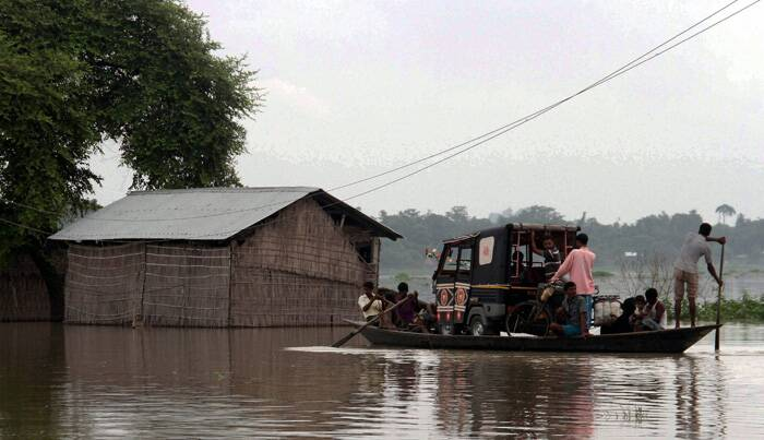Villagers carry an auto rickshaw on a boat to safer areas in flood affected Balimukh village of Morigaon district, Assam on Sunday. (Source: PTI)