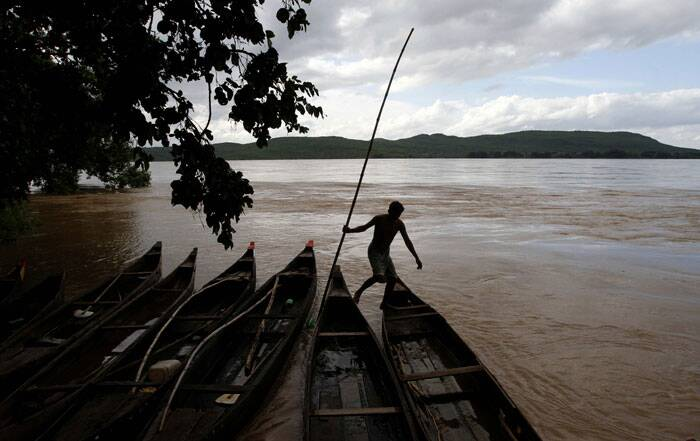 Flood situation turned grim in Odisha with water rising alarmingly in Mahanadi river system prompting the state government to step up rescue operation on a war footing with 23 people killed in rain and flood so far. <br /><br /> A fisherman anchors his boat on the banks of the river Mahanadi flooded after monsoon rains near Mundali, outskirts of Bhubaneswar. (Source: AP)