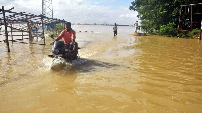 A motorcyclist moves through the flood water in Khurda district of Odisha on Tuesday. (Source: PTI)