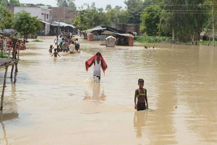 People wade through a flooded road in Barabakni district, Uttar Pradesh on Sunday. (Source: PTI)
