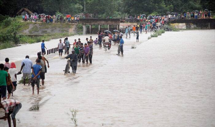 People wade through a low bridge over which flood water of river Bhargavi runs on the outskirt of Bhubaneswar.   (Source: PTI)