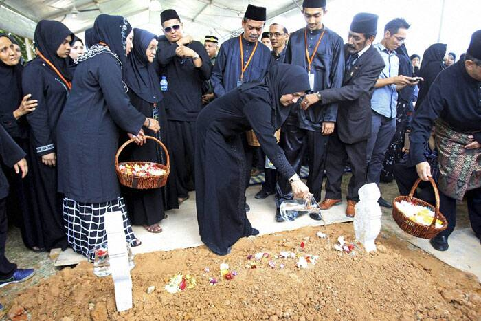 Sharom Ibrahim, center, mother of Nur Shazana, a Malaysia Airlines crew member who was among the victims onboard Flight MH17, pours water on her grave during a burial ceremony at Taman Selatan Muslim cemetery in Putrajaya, Malaysia. (Source: AP)