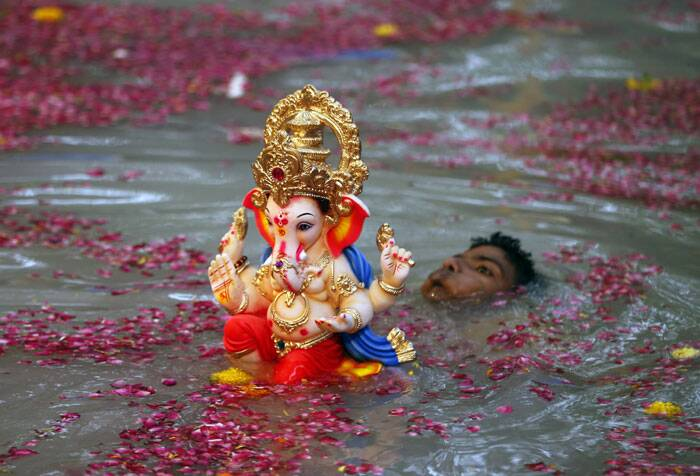 A devotee carries an idol Ganesha for immersion in a water body on the second day of the ten-day Ganesh festival in Mumbai. (Source: AP)
