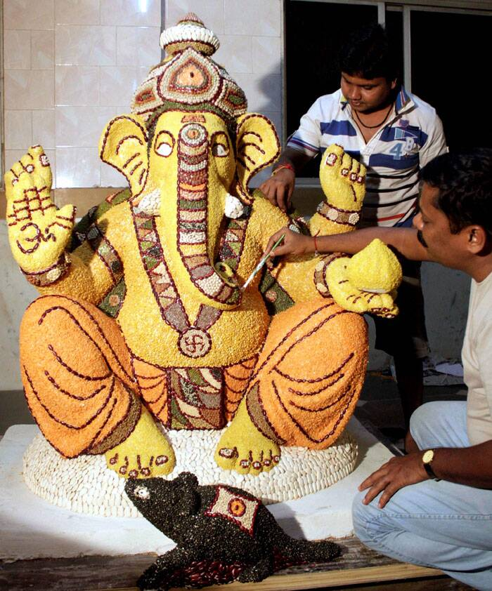 Artists paint a Ganesh idol made of grains in Navi Mumbai. (Source: PTI)
