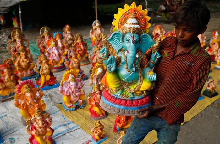 A boy holds a colourful Ganesh idol in his arms at the stall selling the statues in Allahabad. (Source: AP Photo)