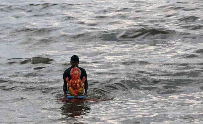 A devotee carries Ganesha idol for immersion in a water body on the second day of the ten-day Ganesh festival in Mumbai. (Source: PTI)