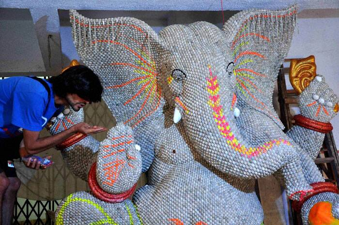 An artisan puts finishing touches on a Ganesh idol made of shells on the eve of Ganesh Chaturthi in Mumbai.  (Source: PTI)