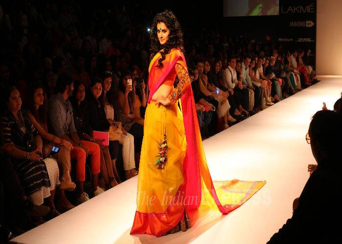 The actress looked beautiful in a bright yellow and tangerine sari with pink as she posed for photos on the ramp. (Source: Express Photo by Pradip Das)