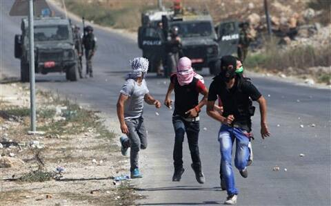 Palestinian protesters run away from Israeli soldiers during clashes, following a demonstration against the Israeli military action in Gaza. (Source: AP photo)