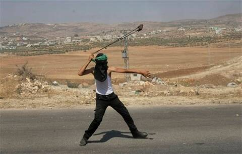 A Palestinian protester throws a stone towards Israeli soldiers during clashes, following a protest against the Israeli military action in Gaza. Source: AP photo