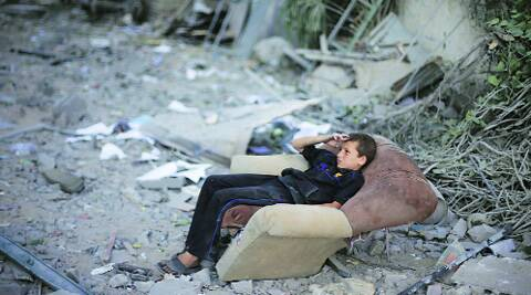 A Palestinian boy sits in a sofa outside his family's house, destroyed in an Israeli air strike, in Gaza City Saturday. Source: Reuters