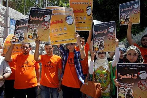Palestinian activists hold posters during a demonstration calling for a boycott of Israeli products to protest Israel's military action in Gaza. (Source: AP photo)