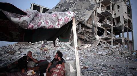 Palestinian Ziad Rizk, 38, left, sits with others in a shelter made of a blanket stretched over four boles next to one of the destroyed Nada Towers, where he lost his apartment and clothes shop, in the town of Beit Lahiya, northern Gaza Strip. Source: AP Photo