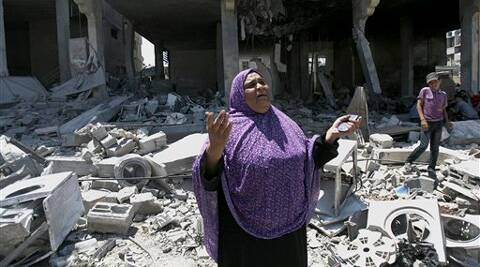 A Palestinian woman gets emotional as she stands on the rubble of a house belong to al Akhras family after it was hit by an Israeli strike in Rafah refugee camp, in the southern Gaza Strip.