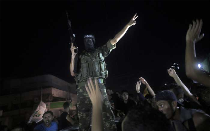 A masked militant flashes the victory sign surrounded by Palestinians celebrate the ceasefire in Gaza City. (Source: AP)