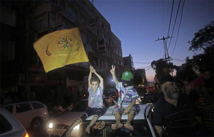 Two Palestinian children sit on top of a car one holding a yellow Fatah movement flag to celebrate the ceasefire in Gaza City. (Source: AP)