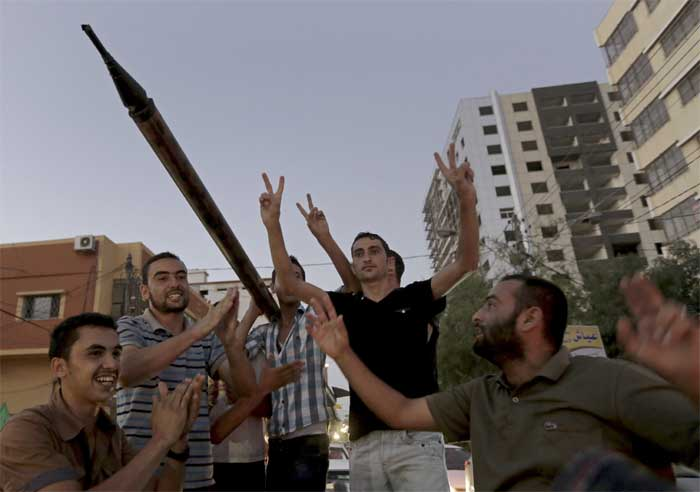 Palestinian Hamas supporters chant slogans while carrying a handmade rocket launcher as they celebrate the ceasefire between Palestinians and Israelis at the main road in Gaza. (Source: AP)