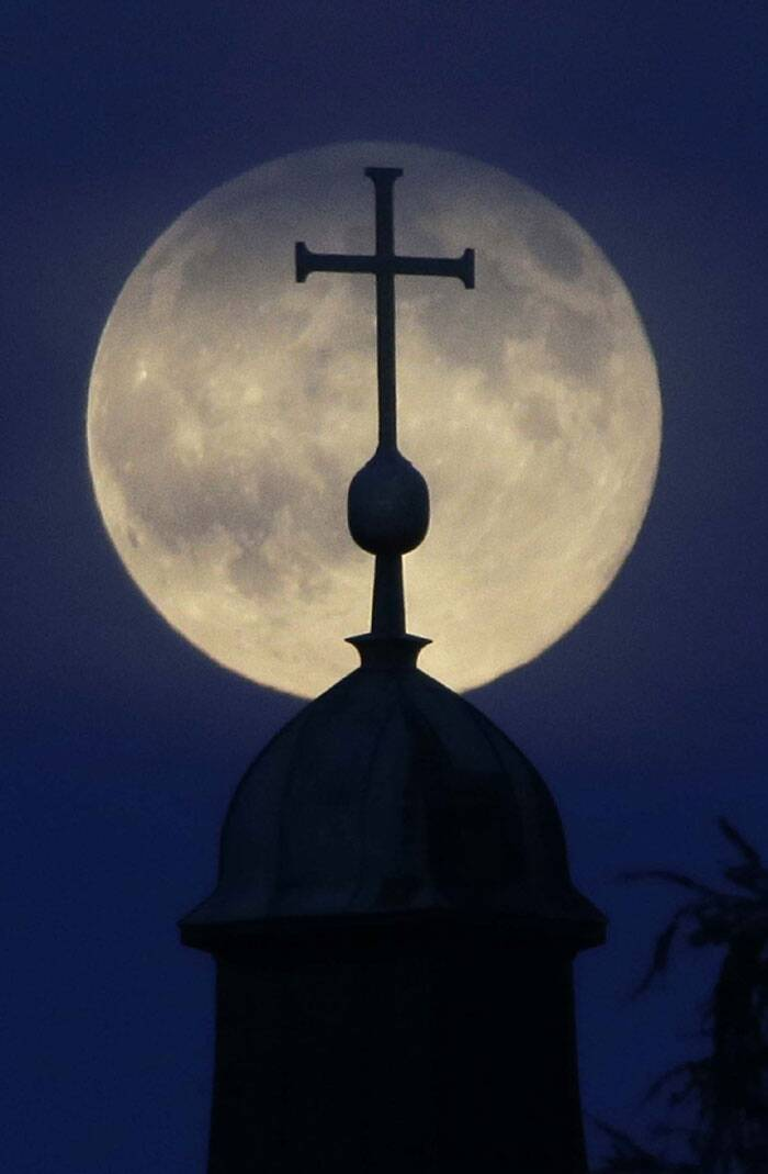 The supermoon appears behind a cross of the 'Christkoenig' church in Munich, southern Germany. (Source: AP)